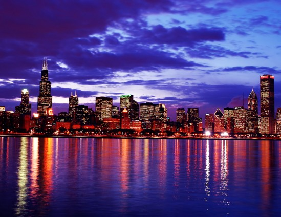 The color-drenched Chicago skyline relects on the water at dusk.