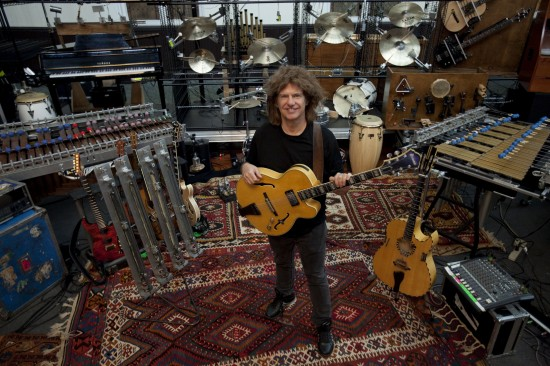 Pat Metheny standing, surrounded by the mechanized instruments that make up his Orchestrion tour.