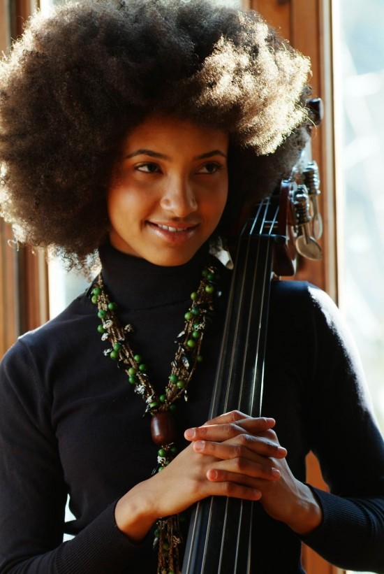 Esperanza Spalding, dressed in a smart black turtleneck and bead necklace, poses with her hands wrapped around the fretboard of her bass, her trademark hair swirling about her head in a display of ordered chaos.