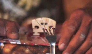 Violin made of trash, closeup on the bridge made from a fork.